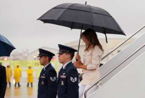 a group of people standing in the rain holding an umbrella: U.S. first lady Melania Trump arrives at airport near the U.S.-Mexico border in McAllen, Texas