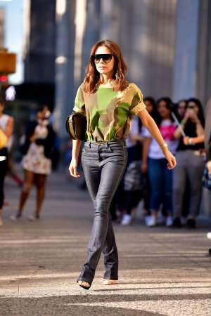 a woman is walking down the street: Victoria Beckham wearing camouflage