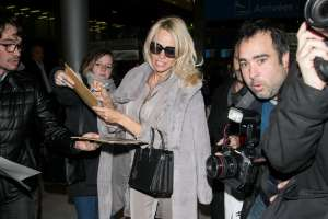 PARIS, FRANCE - DECEMBER 17:  Actress Pamela Anderson signs autographs as she arrives at Charles-de-Gaulle airport on December 17, 2016 in Paris, France.