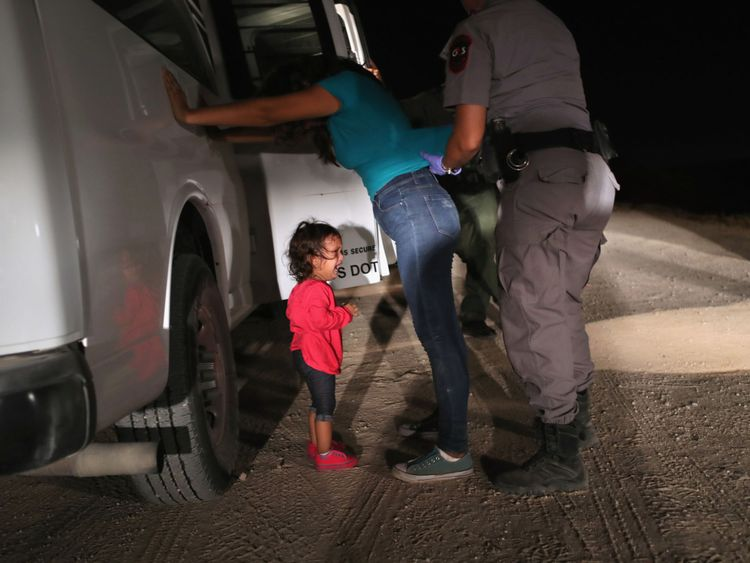 A toddler cries as her mother is searched at the border