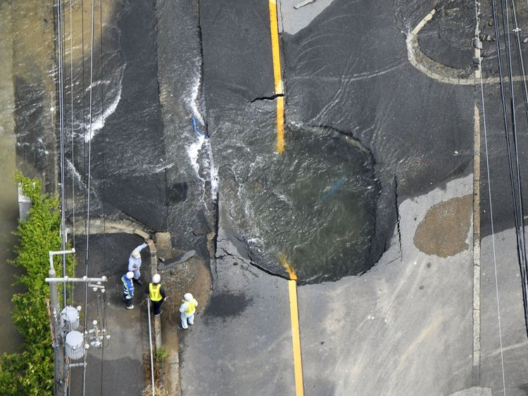 Water flows out from cracks in a road damaged by the earthquake