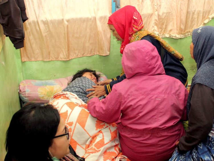 A survivor is surrounded by family members after she was rescued from the ferry