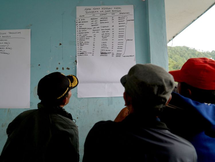 Family members look at a survivor list at the Lake Toba ferry port