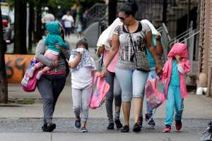 Two woman accompany children to the Cayuga Centers in New York, Thursday, June 21, 2018.