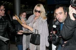 PARIS, FRANCE - DECEMBER 17:  Actress Pamela Anderson signs autographs as she arrives at Charles-de-Gaulle airport on December 17, 2016 in Paris, France.