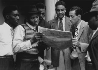 Passengers on the SS Empire Windrush reading a newspaper