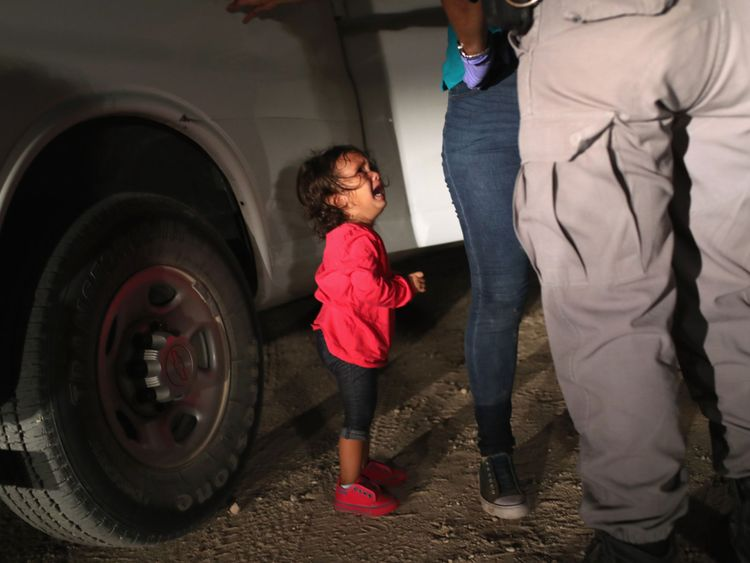 A two year old Honduran asylum seeker cries as her mother is searched and detained