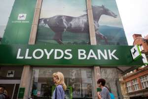 a group of people standing in front of a store: Lloyds is cutting back office staff this time