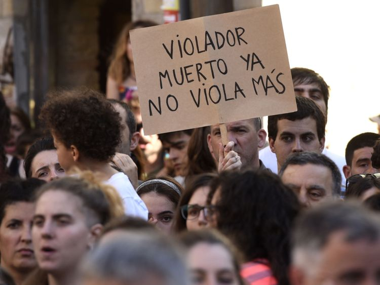 A woman holds a placard that reads: 'A dead rapist does not rape anymore'
