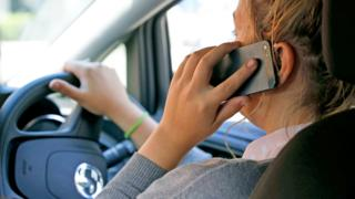 Woman driving while on a mobile phone